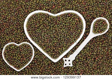 Mung beans in heart shaped porcelain dishes and porcelain spoon forming an abstract background.