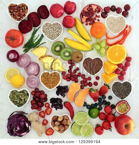 Paleolithic diet health and superfood of fruit, vegetables, nuts and seeds on distressed white wooden background, high in vitamins, anthocyanin, antioxidants, dietary fiber and minerals.