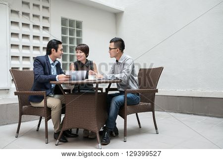 Vietnamese business team having meeting in outdoor cafe