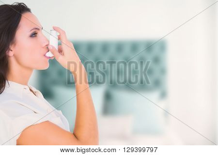 Asthmatic brunette using her inhaler against pillow in a bed