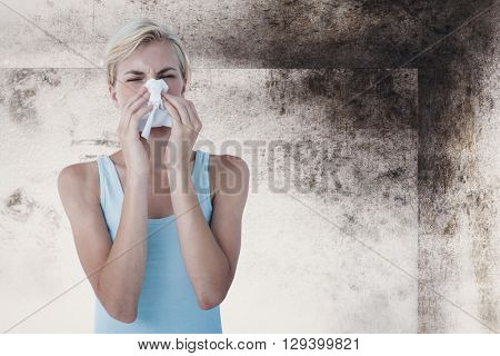 Portrait of woman blowing her nose against image of room corner