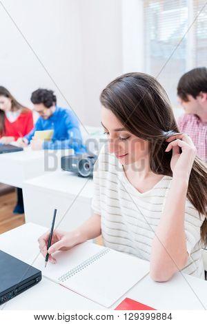 Student woman writing test in seminar room of university or having exam