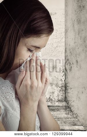 Portrait of woman blowing her nose against image of a room corner