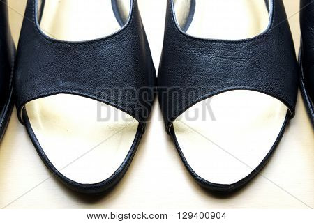 Close up of woman leather shoes with black color on wooden floor.