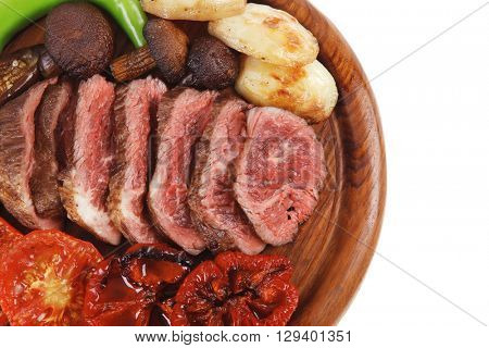 fresh grilled bbq beef meat rib eye steak on wooden plate with baked tomatoes mushroom, potatoes, hot chili pepper isolated on white background empty space for text