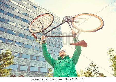 people, sport, style, leisure and lifestyle - happy young hipster man rising up and holding fixed gear bike s in city