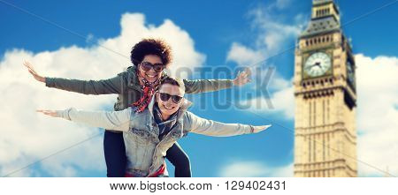 friendship, leisure, international, freedom and people concept - happy teenage couple in shades having fun over london big ben tower background