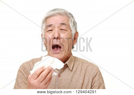 portrait of senior Japanese man with an allergy sneezing into tissue on white background