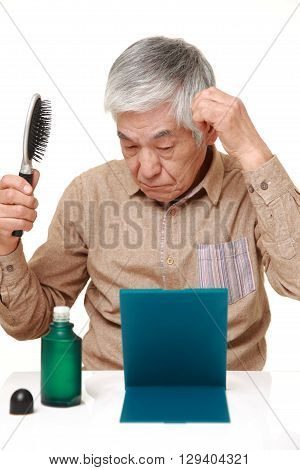 portrait of senior Japanese man using hair restorer on white background
