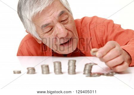 portrait of stack of coins  collapsed when man put a coin on white background