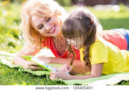 Mother with child daughter reading a book in summer park