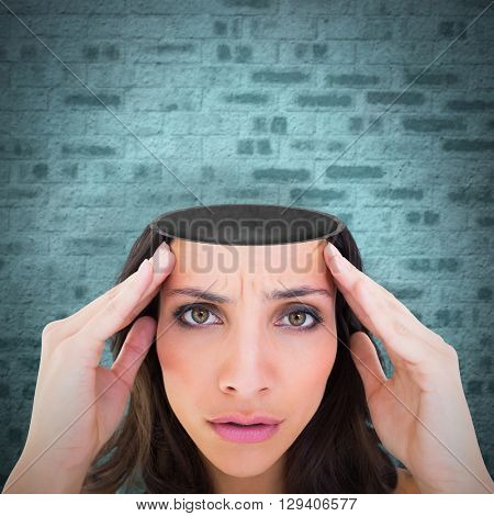 Pretty brunette with a headache against stone wall
