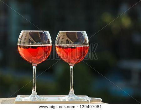 Two glasseses of rose wine, dark green bavkground