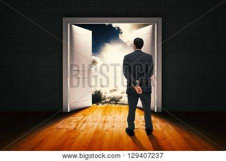 Rear view of classy businessman posing against door opening in dark room to show sky