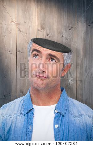 Confused man with grey hair thinking against bleached wooden planks background