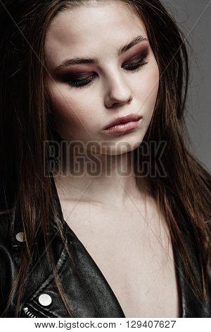 Beautiful woman portrait in rock style, smoky eyes makeup