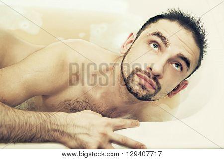 Young Man Lying In A Bathtub