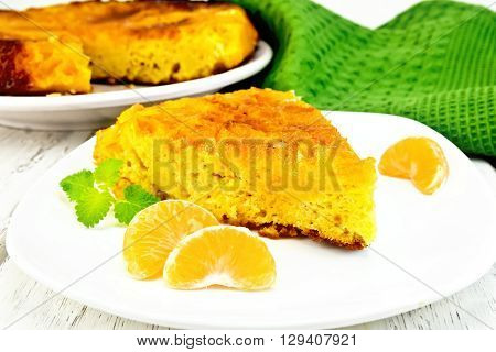 Tart with mandarin mint mandarin slices in a white plate towel on a background of wooden boards