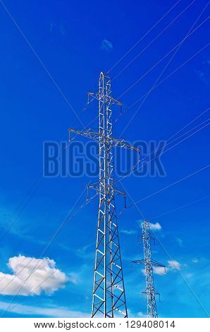 A number of pylons high-voltage power lines against the blue sky and white clouds