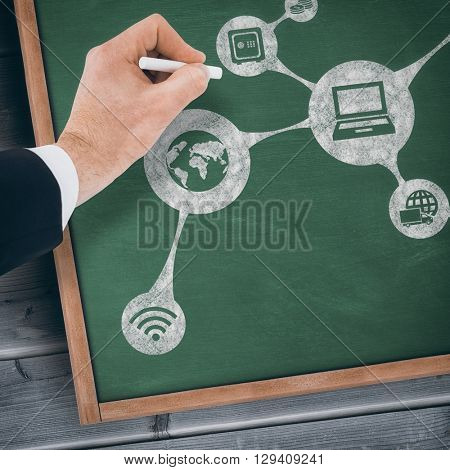 Hand of businessman writing with a white chalk against blackboard with copy space on wooden board