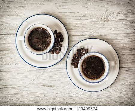 Two ceramic cups of coffee on the wooden background. Coffee beans. Stylish still life. Refreshment theme.