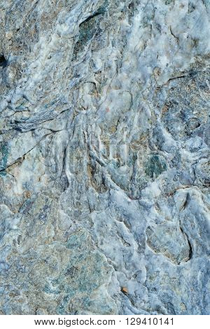 Portrait of a stone. Stone wavy texture with the influx of quartz gray white color.