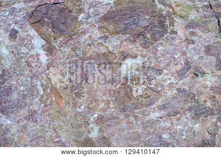 Portrait of a stone. Stone cracked texture of red and brown color with splashes of white quartz.