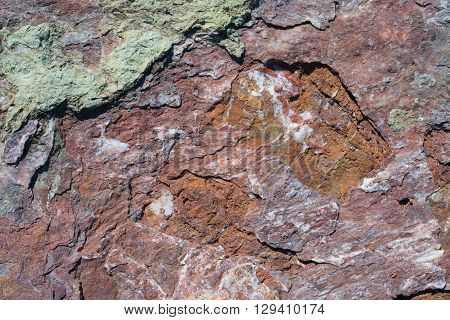 Portrait of a stone. Stone texture of red and brown color with splashes of white quartz.