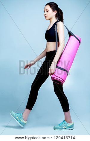 beautiful teenage girl wearing sports clothes going with a yoga mat