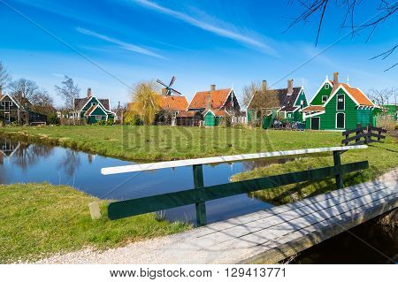 Zaanse Schans, Holland traditional village houses and bridge, windmill  against blue sky