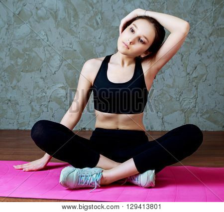 young sporty woman stretching the musles of her neck