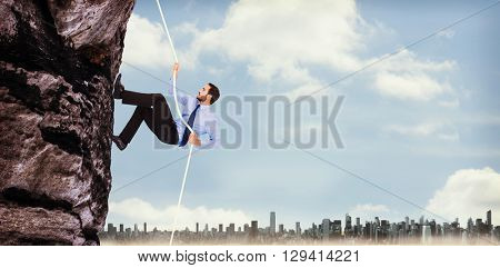Businessman pulling a rope with effort against large city on the horizon