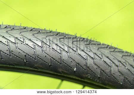 close-up of the bicycle tire texture with the green background
