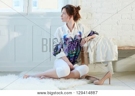 Attractive young woman sitting on floor at home, turning head away, daydreaming.