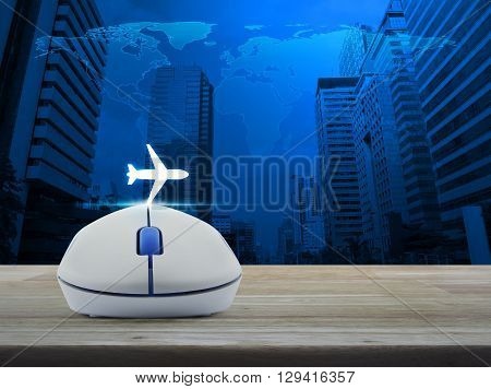 Wireless computer mouse with airplane icon on wooden table in front of map and city tower Airplane transportation concept Elements of this image furnished by NASA