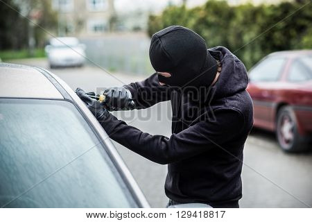 Car Thief Trying To Break Into A Car With A Screwdriver.
