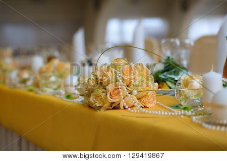 Floral decoration on the table. Arrangement of yellow roses and pearl beads on a wedding table.