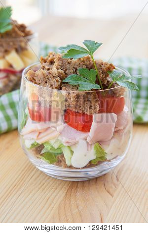 Sandwich in a glass with ham and tomato