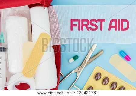 Medical equipment on light blue background with First Aid text on unrolled gauze