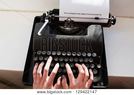 The word your company was highly recommended by against womans hand typing on typewriter