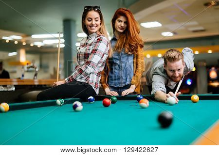 Happy friends enjoying playing pool together in a club
