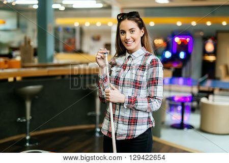 Beautiful young brunette woman chalking billiard cue