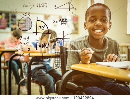 Maths against disabled pupil smiling at camera in classroom