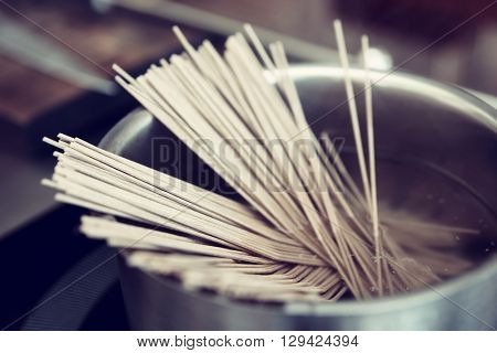 Buckwheat noodles being cooked on induction stove, toned image