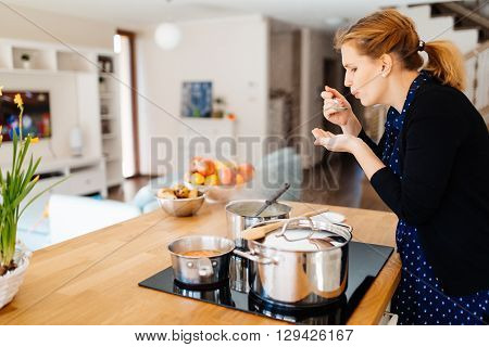 Housewife tasting food being made in modern kitchen
