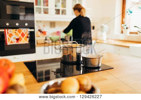 Housewife making  and cooking lunch in modern kitchen