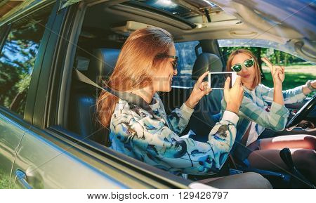 Happy young woman taking photo with a smartphone to her friend showing victory sign inside of car. Female friendship and leisure time concept.