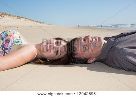 Portrait Of Cute Couple Joining Heads Together On Beach Sand.