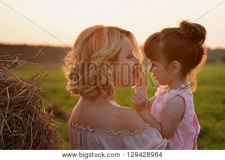 Mother and daughter in the same style in a field, sunset light. Tenderness and hugs