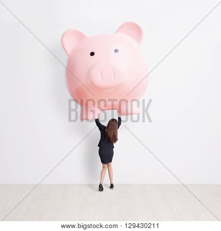 business woman lift heavy pink piggy bank with white wall background great for your design or text asian